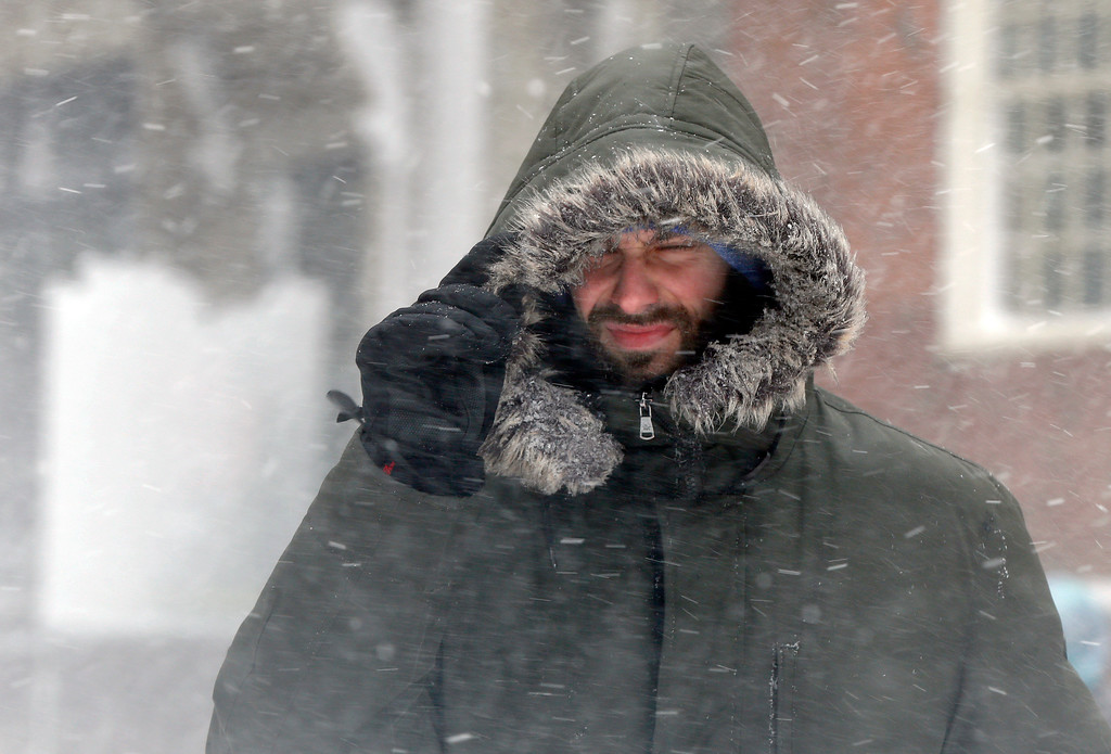 . A man walks through swirling snow during a snowstorm, Tuesday, March 13, 2018, in Boston. A nor\'easter that could deliver up to 2 feet of snow to some areas socked New England on Tuesday, delivering blizzard conditions to parts of Massachusetts and knocking out power to tens of thousands. (AP Photo/Michael Dwyer)