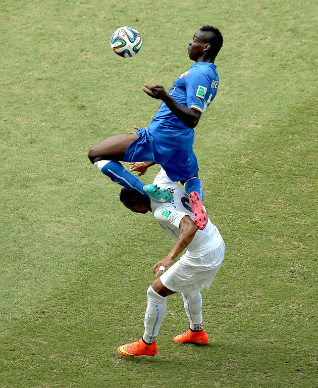 . Italy\'s Mario Balotelli, top, jumps onto Uruguay\'s Alvaro Pereira during the group D World Cup soccer match between Italy and Uruguay at the Arena das Dunas in Natal, Brazil, Tuesday, June 24, 2014. (AP Photo/Hassan Ammar)