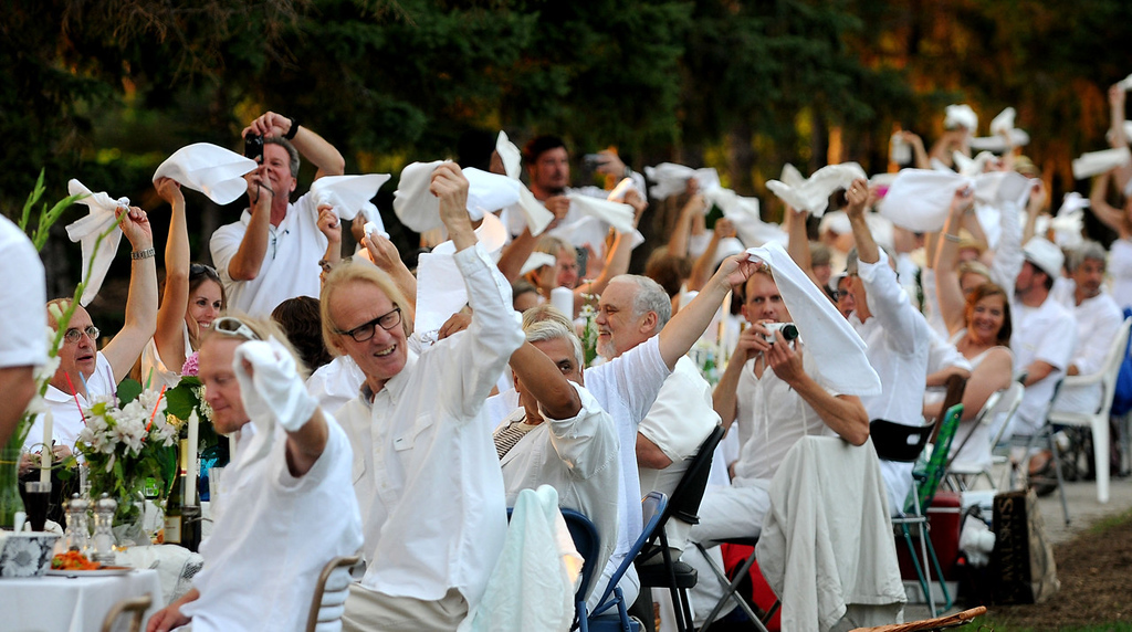 ". White-clad diners signal for the start of their supper. The event is modeled after ""Diner en Blanc,\"" a 25-year tradition in France. (Pioneer Press: Sherri LaRose-Chiglo)"