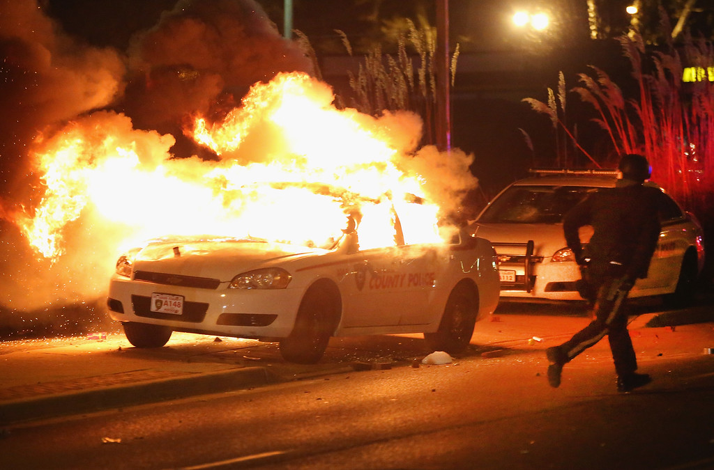 . A police officer runs from a burning squad car after it was set on fire by demonstrators during a protest following the grand jury announcement on November 24, 2014 in Ferguson, Missouri. Ferguson has been struggling to return to normal after Brown, an 18-year-old black man, was killed by Darren Wilson, a white Ferguson police officer, on August 9. His death has sparked months of sometimes violent protests in Ferguson. A grand jury today declined to indict officer Wilson.  (Photo by Scott Olson/Getty Images)