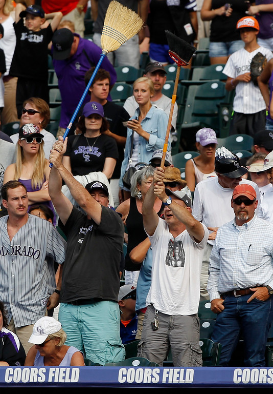 . Colorado Rockies fans wave brooms after the team\'s 3-2 victory over the Pittsburgh Pirates in a baseball game in Denver, Sunday, Aug. 11, 2013. The Rockies swept the three-game weekend series against the Pirates who came to Colorado with the best record in Major League Baseball. (AP Photo/David Zalubowski)