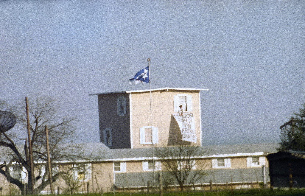 . A person inside of the tower of the Branch Davidian compound removes a banner from the guard tower so a new one can be put in place in Waco, Texas on April 8, 1993. Several banners have been placed on the compound since the February 28 siege. (AP Photo/David Phillip)
