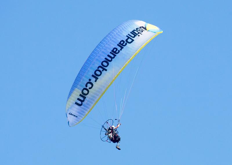 A Paramotor pilot flies overhead.