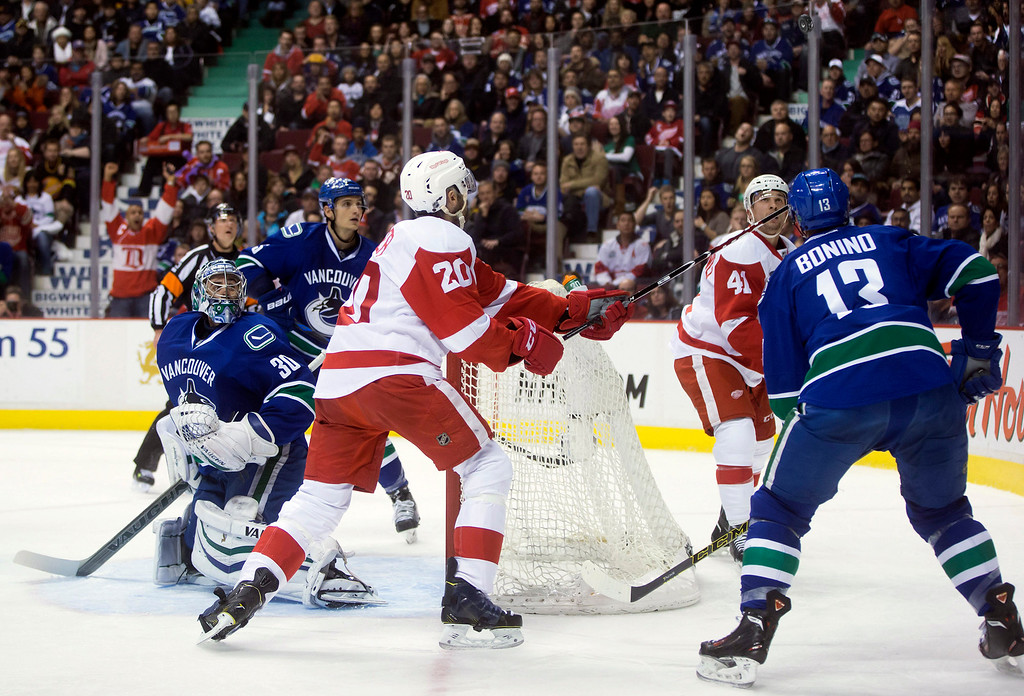 . Vancouver Canucks\' goalie Ryan Miller, from left, Luca Sbisa, of Switzerland, Detroit Red Wings\' Drew Miller (20), Luke Glendening (41) and Canucks\' Nick Bonino (13) watch the puck after Miller made a save and it deflected over the net during the first period of an NHL hockey game in Vancouver, British Columbia on Saturday, Jan. 3, 2015. (AP Photo/The Canadian Press, Darryl Dyck)