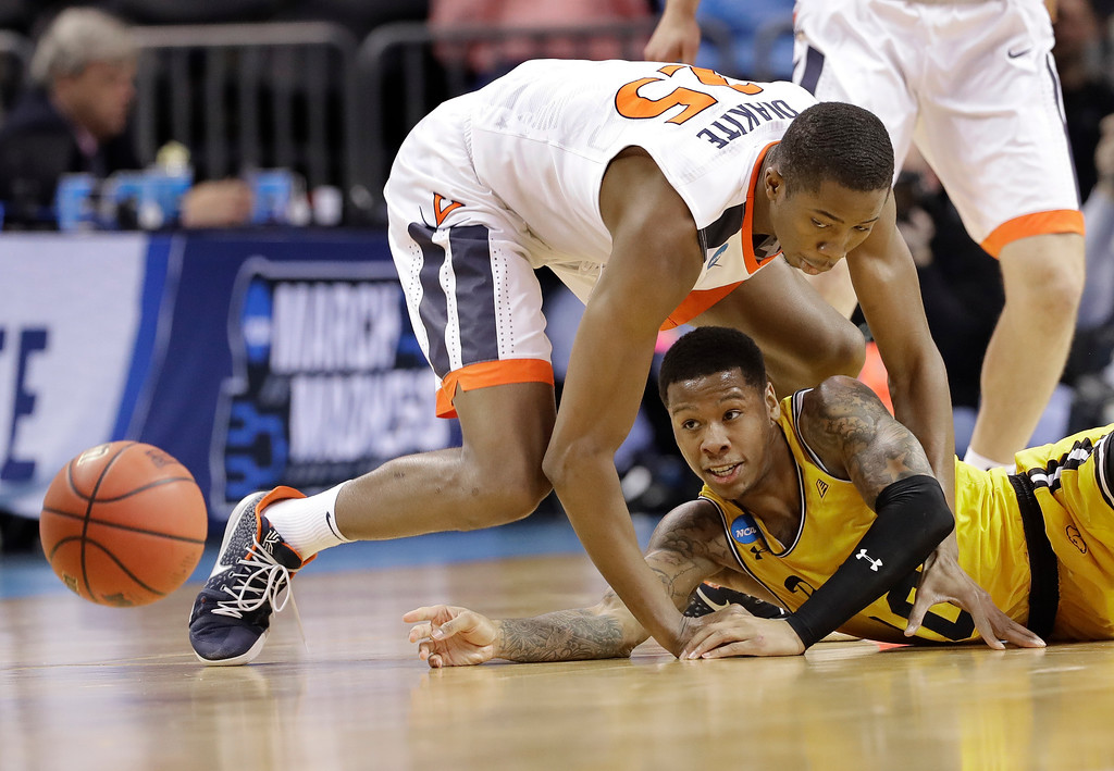 . UMBC\'s Jairus Lyles (10) passes the ball as Virginia\'s Mamadi Diakite (25) defends during the first half of a first-round game in the NCAA men\'s college basketball tournament in Charlotte, N.C., Friday, March 16, 2018. (AP Photo/Gerry Broome)