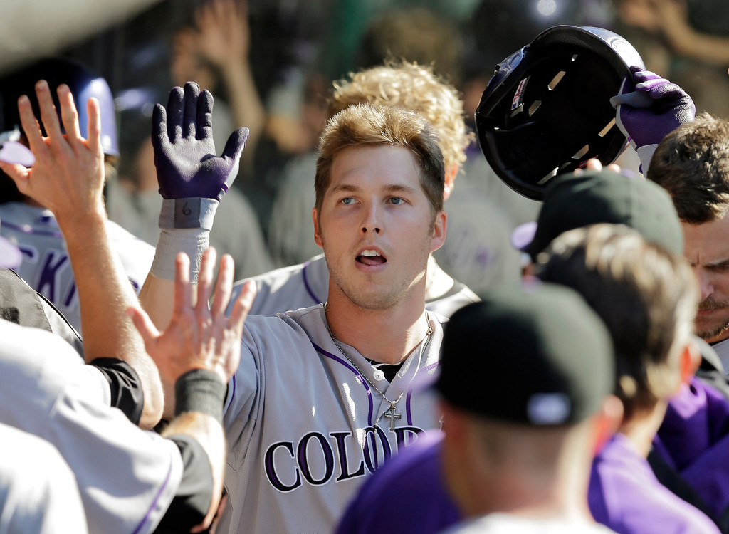. Colorado Rockies\' Corey Dickerson is congratulated in the dugout after a solo home run off Cleveland Indians relief pitcher Scott Atchison in the seventh inning of a baseball game Saturday, May 31, 2014, in Cleveland. (AP Photo/Mark Duncan)