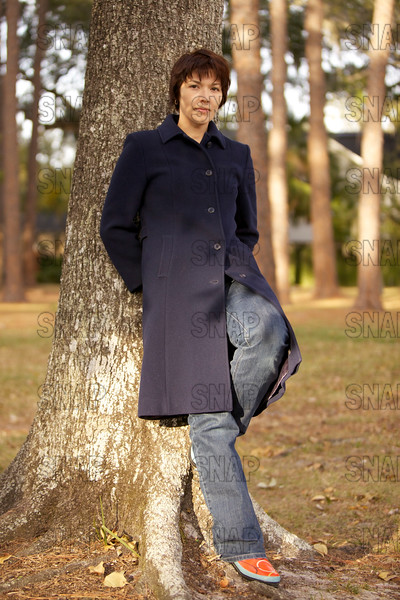 A beautiful young woman leans against a tree in the winter.