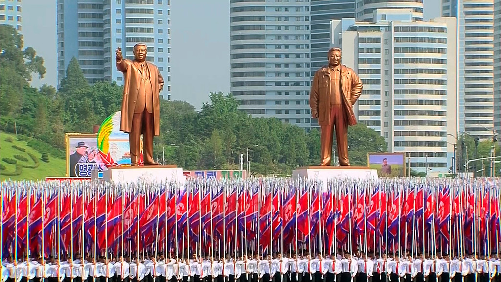 . In this image taken from video North Koreans carry North Korean flags in front of statues of the late leaders Kim Il Sung, left, and Kim Jong Il, during a military parade marking the 65th anniversary of the country\'s founding, Monday, Sept. 9, 2013, in Pyongyang, North Korea. (AP Photo/KRT via AP Video)