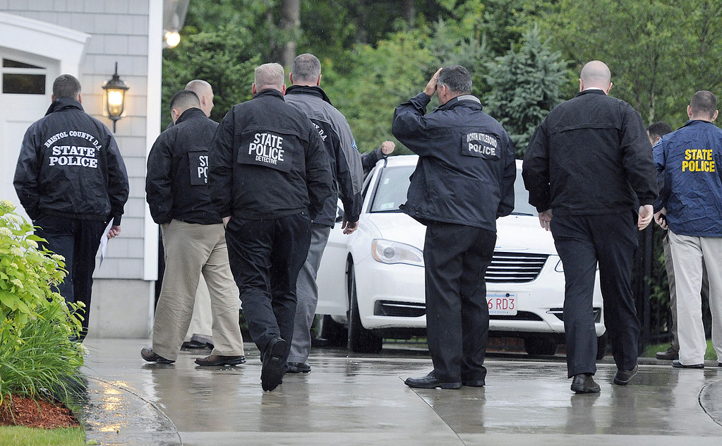 . In this Tuesday, June 18, 2013 photo, state and local police gather outside the home of New England Patriot\'s NFL football player Aaron Hernandez in North Attleborough, Mass.  Police spent hours at the home Tuesday as another group of officers searched an industrial park about a mile away where a body was discovered the day before.  (AP Photo/The Sun Chronicle, Martin Gavin)