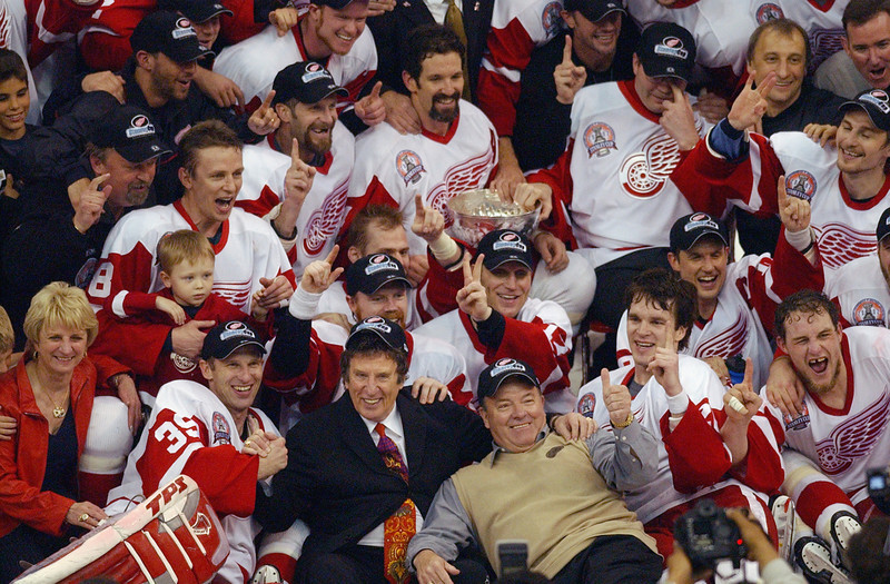 . DETROIT, MI - JUNE 13:  The Detroit Red Wings owner Mike Ilitch, head coach Scottie Bowman and the rest of the team pose with the Stanley Cup after defeating the Carolina Hurricanes 3-1 in game five of the NHL Stanley Cup Finals on June 13, 2002 at the Joe Louis Arena in Detroit, Michigan. (Photo by Harry How/Getty Images/NHLI)