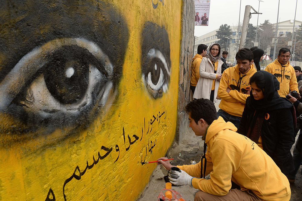 . Afghan street artists paint a mural as part of an event to mark International Women\'s Day in Kabul on March 8, 2014. In Kabul and major cities in Afghanistan, enormous progress has been made in women\'s rights since the 2001 US-led invasion brought down the Taliban regime that banned girls from going to school and women from working. But in remote areas where the traditional patriarchal system is very much the norm, life for most women has barely improved at all. (SHAH MARAI/AFP/Getty Images)
