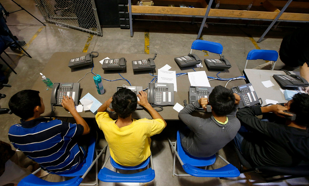 . A few boys try to make calls as they are joined by hundreds of mostly Central American immigrant children that are being processed and held at the U.S. Customs and Border Protection Nogales Placement Center on Wednesday, June 18, 2014, in Nogales, Ariz.  (AP Photo/Ross D. Franklin, Pool)