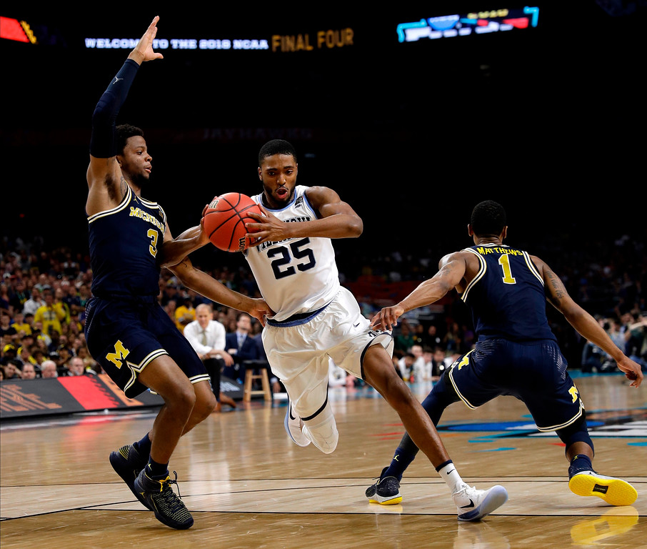 . Villanova guard Mikal Bridges (25) drives to the basket between Michigan\'s Zavier Simpson, left, and Charles Matthews, right, during the second half in the championship game of the Final Four NCAA college basketball tournament, Monday, April 2, 2018, in San Antonio. (AP Photo/David J. Phillip)
