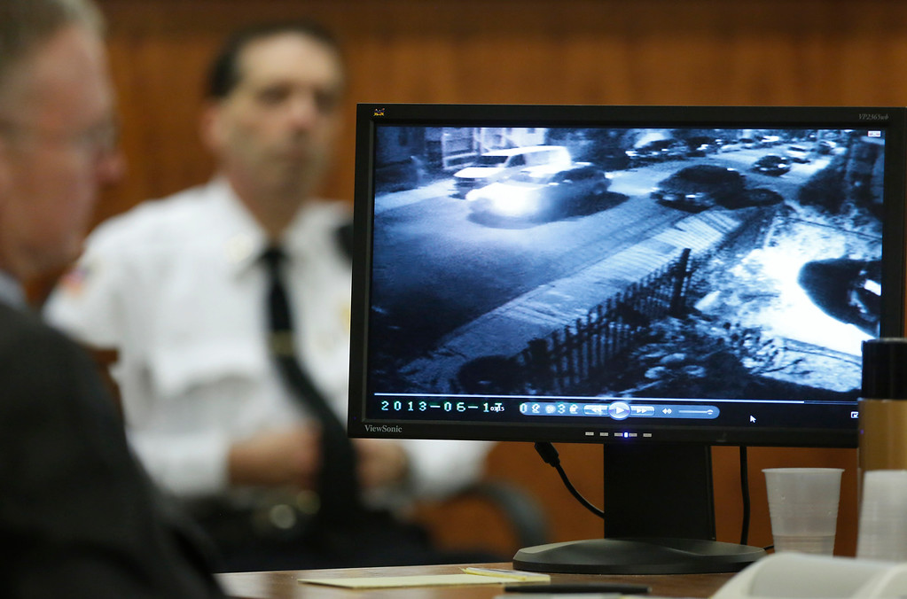 . Charles Rankin, left, defense attorney for former New England Patriots football player Aaron Hernandez, looks on as June 17, 2013 surveillance video outside Odin Lloyd\'s home is displayed on a monitor during Hernandez\'s murder trial Thursday, March 26, 2015, in Fall River, Mass. Hernandez is charged with killing Lloyd. A court officer is seated behind. (AP Photo/Steven Senne, Pool)