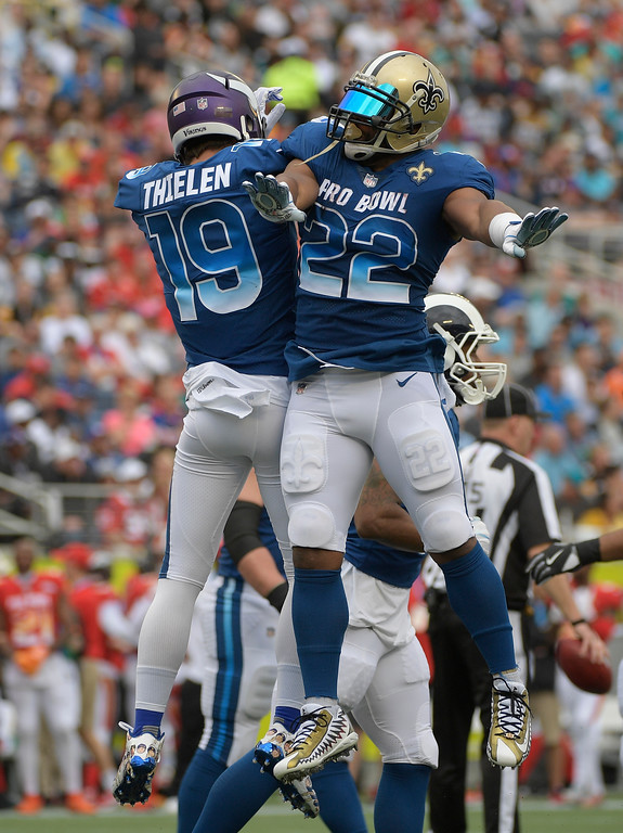 . NFC wide receiver Adam Thielen (19), of the Minnesota Vikings and running back Mark Ingram (22), of the New Orleans Saints, celebrate, after Thielen scored a touchdown, during the first half of the NFL Pro Bowl football game against the AFC, Sunday, Jan. 28, 2018, in Orlando, Fla. (AP Photo/Phelan M Ebenhack)