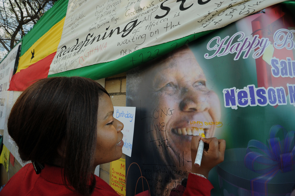 """. A woman leaves a birthday message for former South African president Nelson Mandela outside the Medi Clinic Heart Hospital in Pretoria on July 18, 2013. Nelson Mandela spent his 95th birthday in hospital today but his health was \""""steadily improving\"""", South Africa\'s presidency said, as people around the world honoured his legacy with charitable acts.  ALEXANDER JOE/AFP/Getty Images"""