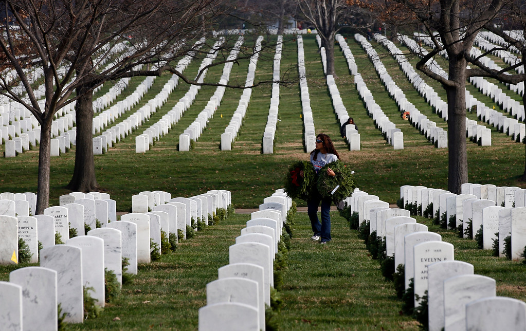 . A volunteer carries wreaths to placed at graves during Wreaths Across America at Arlington National Cemetery, Saturday, Dec. 12, 2015 in Arlington, Va. Organizers estimated that volunteers placed 240,815 wreaths at Arlington. (AP Photo/Alex Brandon)