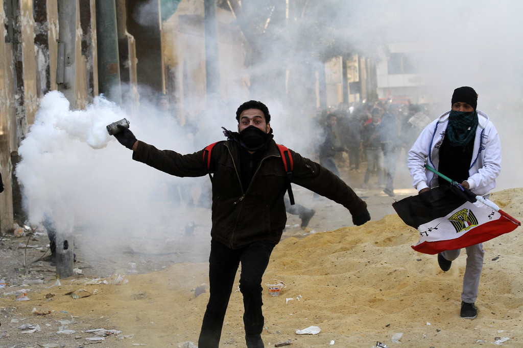 . An Egyptian protester runs to throw tear gas during a protest in Tahrir Square on January 25, 2013 in Cairo. Huge crowds are expected to demonstrate in Egypt on the second anniversary of the revolution that ousted Hosni Mubarak and brought in an Islamist government, as political tensions simmer and economic woes bite. MOHAMMED ABED/AFP/Getty Images