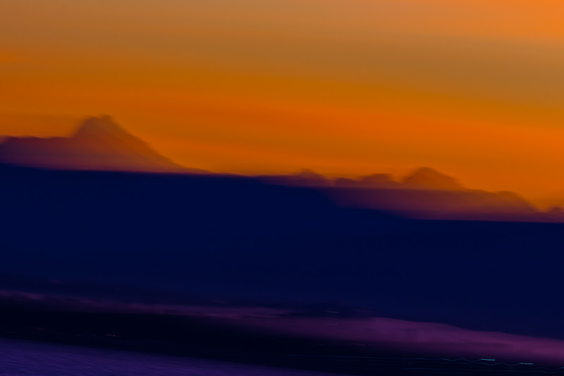 Abstract oranges and purples of mountains and the ocean and clouds
