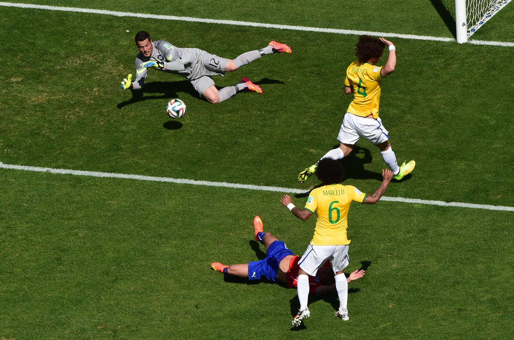 . Brazil\'s goalkeeper Julio Cesar (top) makes a save during the round of 16 football match between Brazil and Chile at The Mineirao Stadium in Belo Horizonte during the 2014 FIFA World Cup on June 28, 2014. (FRANCOIS XAVIER MARIT/AFP/Getty Images)