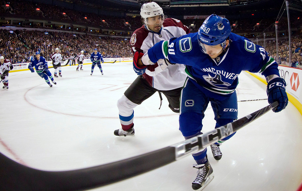 . Colorado Avalanche\'s Ryan O\'Byrne, rear, checks Vancouver Canucks\' Maxim Lapierre during the first period of an NHL hockey game in Vancouver, British Columbia, on Wednesday, Jan. 30, 2013. (AP Photo/The Canadian Press, Darryl Dyck)