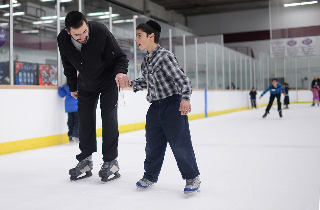 . CENTENNIAL, CO. DECEMBER 25: Rabbi Gadi Levy, left, is ice skating with his son Shimshy Levy, 9, at the the South Suburban Sports Center in Centennial, Colorado on December 25, 2013. For the fourteenth year, the Denver Community Kollel Women\'s Division is offering a Jewish Family Extravaganza of family fun and entertainment.  (Photo by Hyoung Chang/The Denver Post)