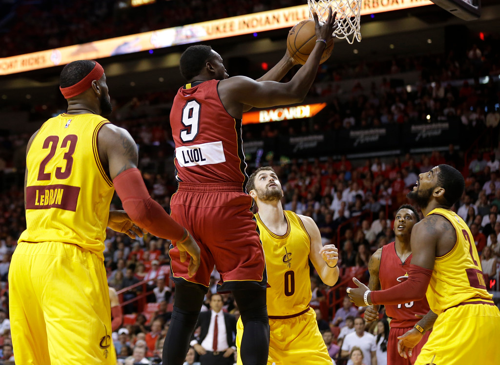. Miami Heat forward Luol Deng (9) grabs a rebound over Cleveland Cavaliers forward LeBron James (23), forward Kevin Love (0), and guard Kyrie Irving (2) during the first half of an NBA basketball game, Thursday, Dec. 25, 2014, in Miami. (AP Photo/Lynne Sladky)