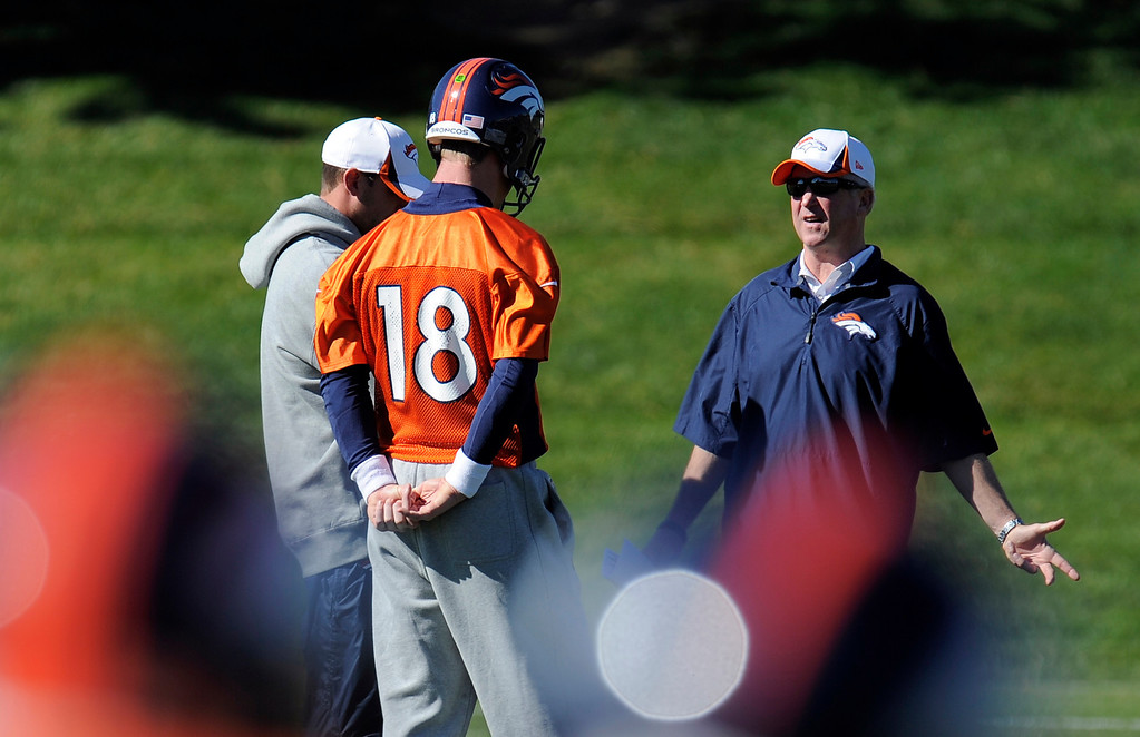 . Denver Broncos quarterback Peyton Manning (18) talks with Denver Broncos head coach John Fox and Adam Gase during practice October 23, 2013 at Dove Valley. Manning talks with Gase while the quarterbacks threw. Peyton did not participate. (Photo by John Leyba/The Denver Post)