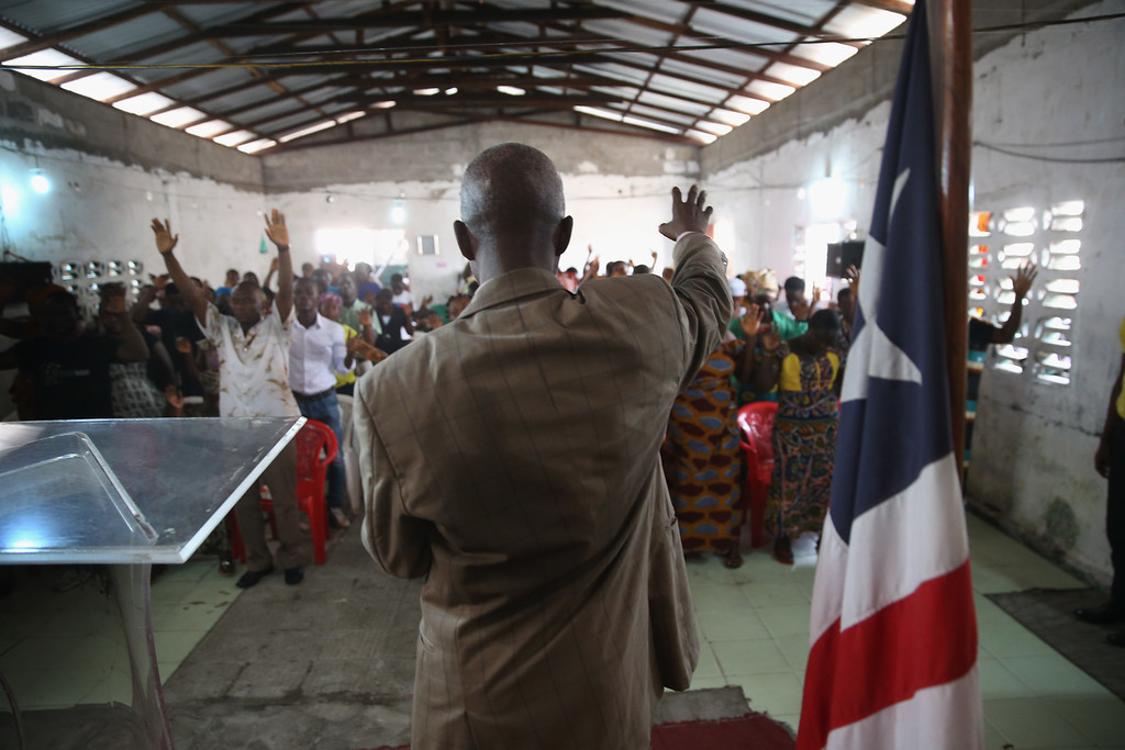 . A pastor leads his congregation in prayer during a Sunday service at the Bethel World Outreach Church in the West Point township on January 25, 2015 in Monrovia, Liberia. With Ebola cases now in single digits nationwide, many Liberians have begun to return to normal life. The government and international aid agencies, however, are urging the public to remain vigilant until the disease is fully eradicated in West Africa. (Photo by John Moore/Getty Images)