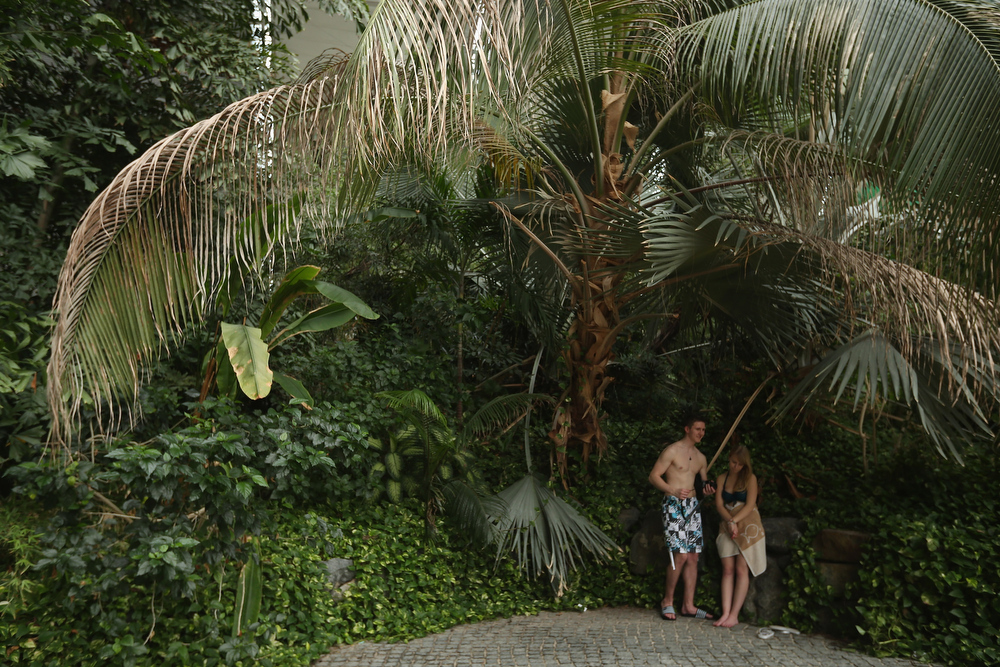 . Young visitors stand under a palm tree at the Tropical Islands indoor resort on February 15, 2013 in Krausnick, Germany. Located on the site of a former Soviet military air base, the resort occupies a hangar built originally to house airships designed to haul long-distance cargo. Tropical Islands opened to the public in 2004 and offers visitors a tropical getaway complete with exotic flora and fauna, a beach, lagoon, restaurants, water slide, evening shows, sauna, adventure park and overnights stays ranging from rudimentary to luxury. The hangar, which is 360 metres long, 210 metres wide and 107 metres high, is tall enough to enclose the Statue of Liberty.  (Photo by Sean Gallup/Getty Images)