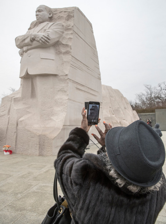 . A visitor snaps a photo at the Martin Luther King Jr. Memorial in Washington, Monday, Jan. 16, 2017. (AP Photo/J. Scott Applewhite)