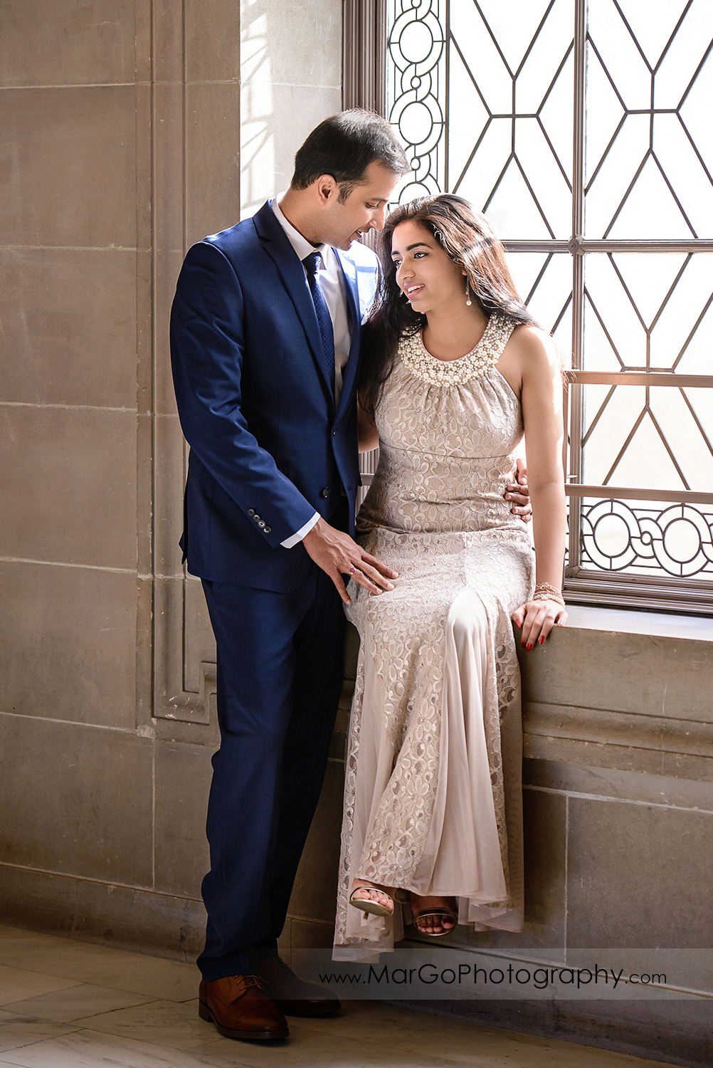 full body portrait of woman in beige dress and man in navy blue suit sitting on the window on the third floor of San Francisco City Hall