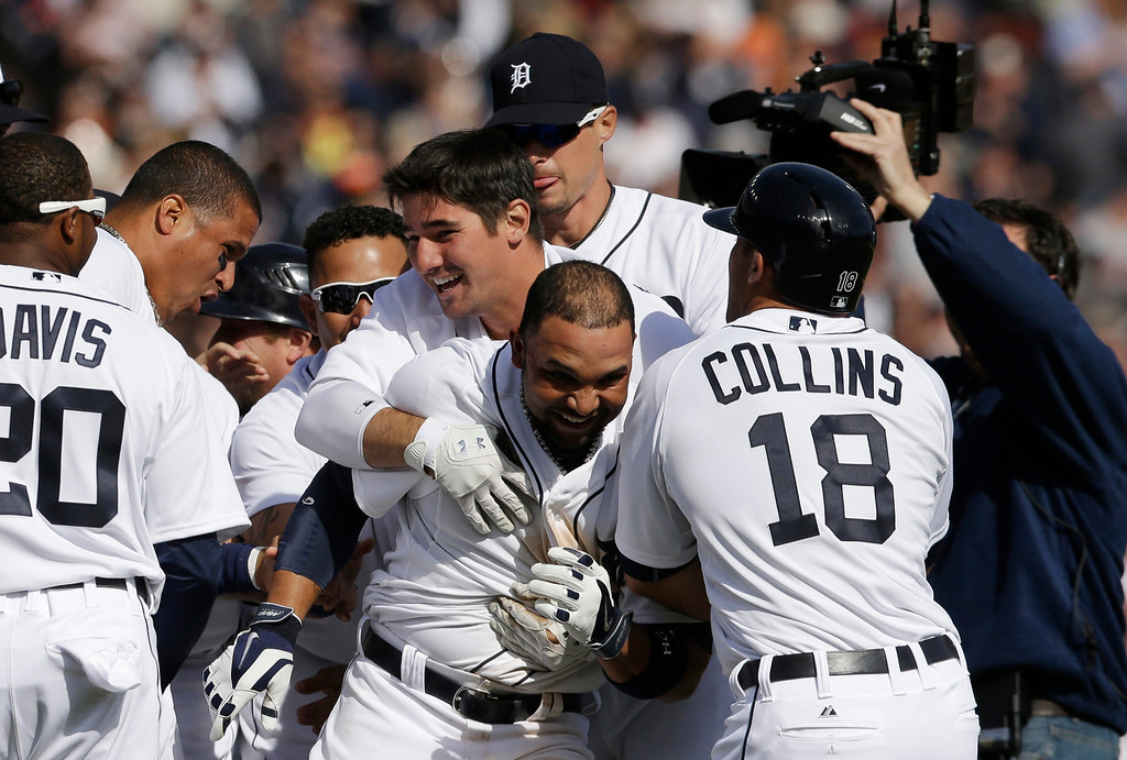 . Detroit Tigers\' Alex Gonzalez, center, is mobbed after hitting the game winning single to score the winning run from third during the ninth inning of a baseball game against the Kansas City Royals in Detroit, Monday, March 31, 2014. (AP Photo/Carlos Osorio)