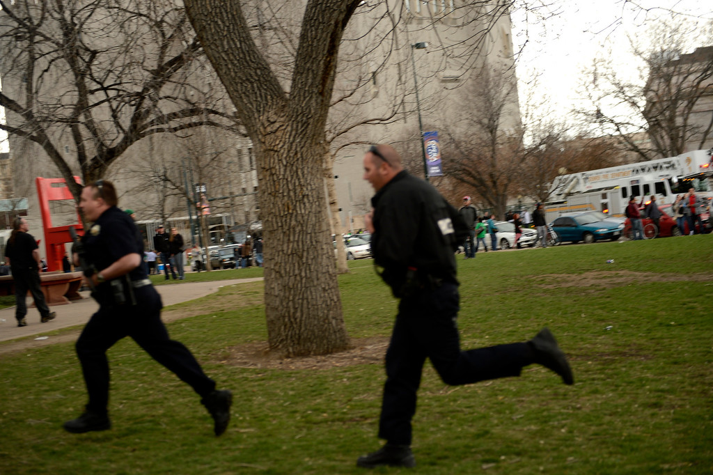 . DENVER, CO. - APRIL 20: April 20: Denver Police officers running to the scene at Civic Center Park in Denver Colorado, Saturday April 20th, 2013 after the 4/20 pot rally. Two people were shot during Saturday\'s annual 4/20 marijuana rally, held on a day cannabis enthusiasts regard as a holiday called 4/20 that drew tens of thousands to Denver\'s Civic Center park. This is the first 4/20 marijuana rally since Colorado voters legalized marijuana use for people 21 and older in November. April 20, 2013 Denver, Colorado. (Photo By Joe Amon/The Denver Post)