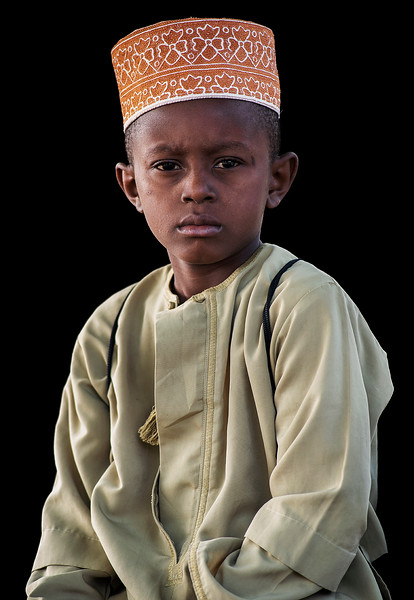 Portrait of a young, Muslim school boy taken on his way to work.  Pangani, Tanzania, 2019.