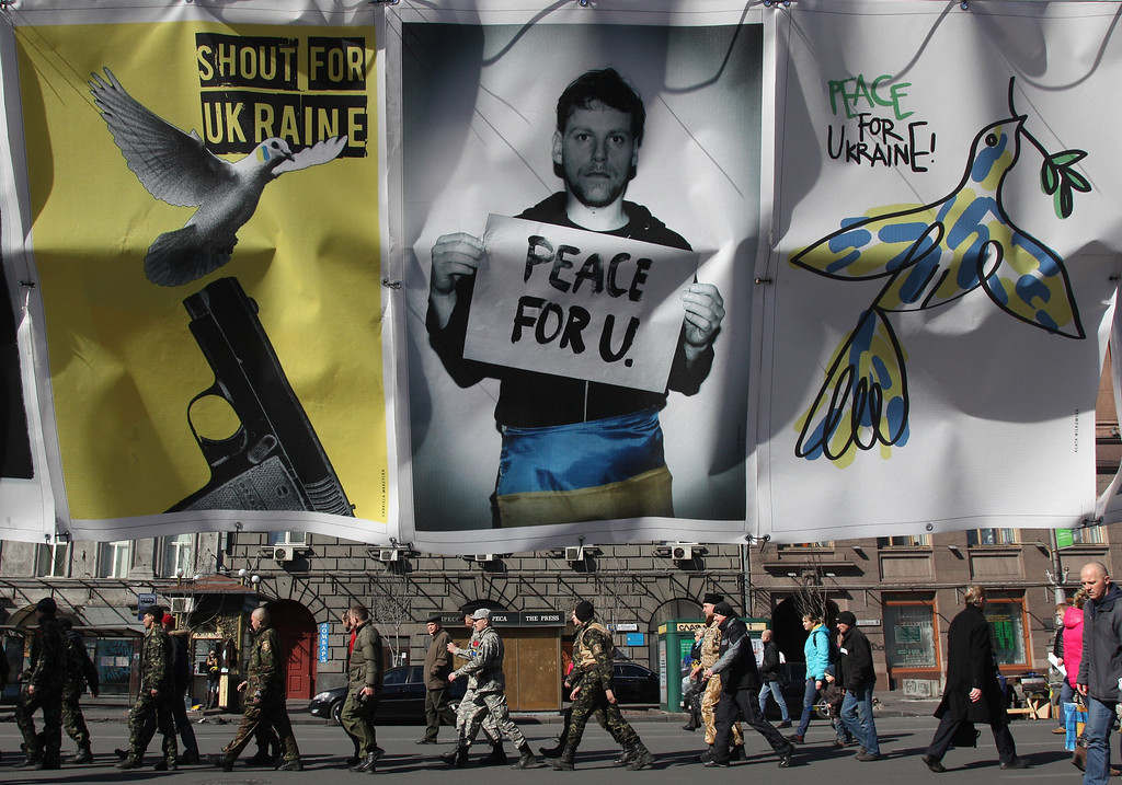 . Maidan self-defense activists walk as anti-war placards are hung in  Kiev on March 13, 2014.  Ukraine moved Thursday to mobilize a volunteer force to ward off Russia\'s expansionist threat. ANATOLII STEPANOV/AFP/Getty Images