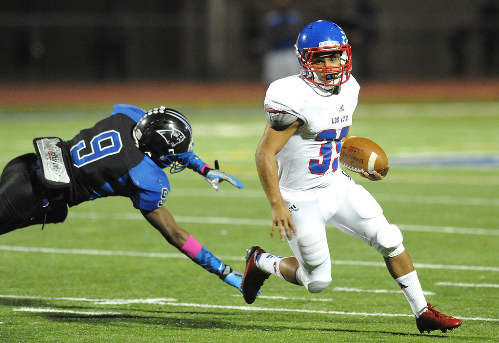 . Los Altos runningback Estuardo Marcos (#35) runs out of the diving reach of Diamond Ranch\'s John Perkins (#9) in their Hacienda League opener football game at Diamond Ranch High School in Pomona on Friday October 4, 2013. (San Gabriel Valley Tribune/Staff Photo by Keith Durflinger)