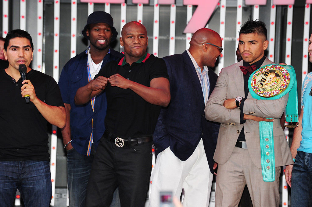 . Floyd Mayweather (3L) gestures as he takes the stage with Victor Ortiz (R) for a pre-fight event at CityWalk in Universal City, California, September 12, 2011. At far left is radio host Piolin and rapper 50 Cent (2L). .  AFP PHOTO / ROBYN BECK (Photo credit should read ROBYN BECK/AFP/Getty Images)