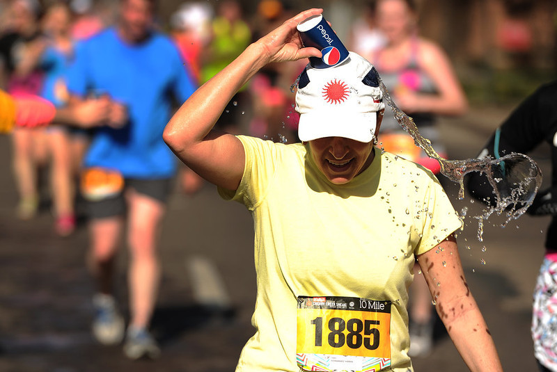 . With only 1/2 mile left to go, runners took advantage of the last water station to drink water or throw it on themselves to cool off.  The 31st annual Cherry Creek Sneak had all sorts of distances for this year\'s race.  The Sneak, as it is affectionately named, had a 10 mile, 5 mile, 3.1 mile or 5K, a 1.5 mile Denver\'s 7 Sprint, and a kid\'s fun run for thousands of competitors, runners and walkers that turned out in the Cherry Creek neighborhood of Denver, CO on April 28, 2013.  The race is always held the last Sunday in April. This year participants cheered the national anthem and observed a moment of silence for victims of the Boston Marathon bombing at the start of each race. (Photo by Helen H. Richardson/The Denver Post)