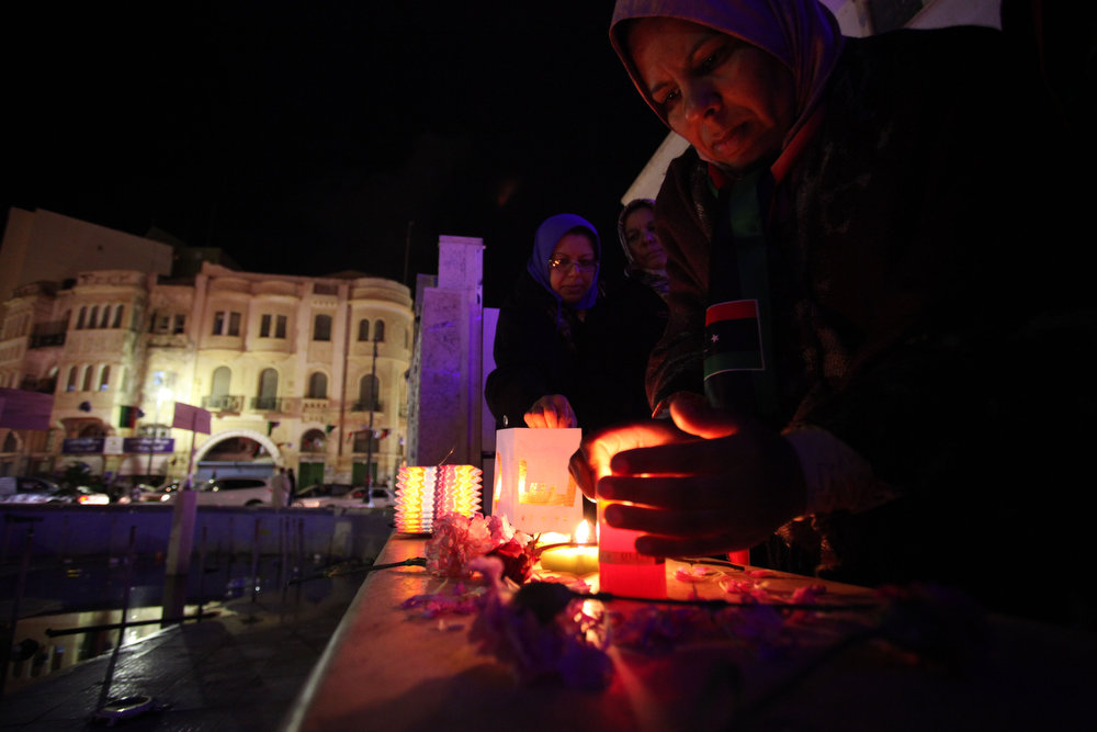 Description of . Libyan women light candles during a vigil for revolution martyrs during a celebration to commemorate the second anniversary of the revolution that ousted Moammar Gadhafi, in Benghazi, Libya, Friday, Feb, 15, 2013.  (AP Photo/Mohammad Hannon)