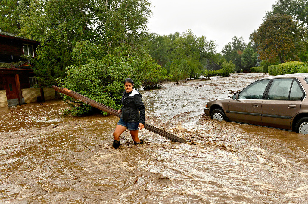 . Sonia Chacon clears debris from around her family\'s home in north Boulder on Sept. 12, 2013. Nearly every road heading into the foothills of Boulder, Larimer and northern Jefferson counties was blocked by floodwaters or debris. Both of Chacon\'s family\'s cars were stuck in a foot of mud, and the first floor of their home was flooded.