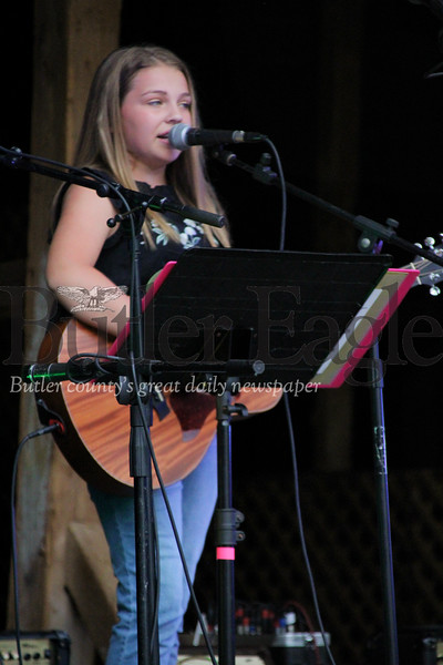 """Alexa Speicher plays the guitar during the """"In Harmony"""" Heritage Music Festival, Saturday, at the Harmonist-Ziegler Barn."""