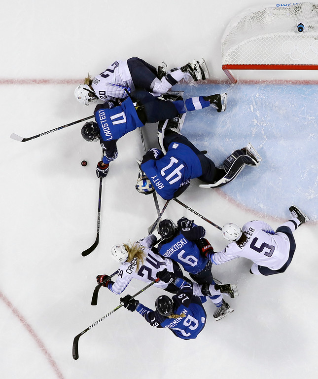 . Rosa Lindstedt (4), of Finland, and Hannah Brandt (20), of the United States, battle for the puck during the second period of the preliminary round of the women\'s hockey game at the 2018 Winter Olympics in Gangneung, South Korea, Sunday, Feb. 11, 2018. (AP Photo/Kiichiro Sato)