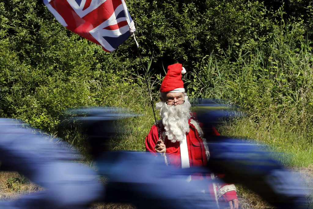 . A supporter disguised as Santa Claus holds a Great Britain\'s union jack national flag as cyclists ride past during the 197 km tenth stage of the 100th edition of the Tour de France cycling race on July 9, 2013 between Saint-Gildas-des-Bois and Saint-Malo, northwestern France.    JOEL SAGET/AFP/Getty Images