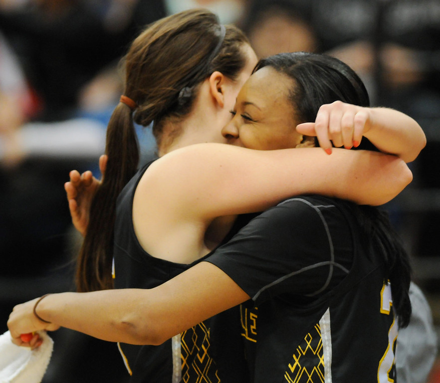 . DeLaSalle center Natalie Eull, left, is hugged by teammate Tyseanna Johnsonas she comes off the floor in the final seconds of DeLaSalle\'s 65-50 victory over Red Wing to claim the Class 3A girls basketball championship Saturday, March 16, 2013, at Target Center. (Pioneer Press: John Autey)