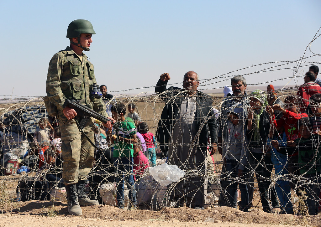 . A Turkish soldier stands guard as several hundred Syrian refugees wait to cross the border in Suruc, Turkey, Sunday, Sept. 21, 2014. (AP Photo/Burhan Ozbilici)