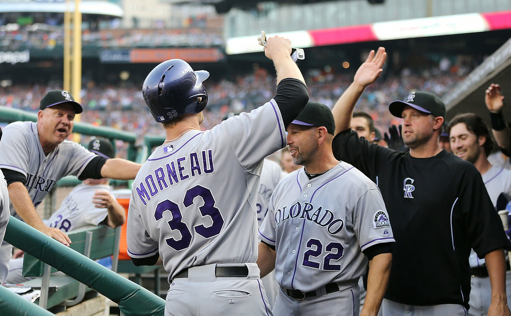 . DETROIT, MI - AUGUST 02: Justin Morneau #33 of Colorado Rockies celebrates with his teammates after scoing on the double by Drew Stubbs (not in photo) during the second inning of the game at Comerica Park on August 2, 2014 in Detroit, Michigan.  (Photo by Leon Halip/Getty Images)