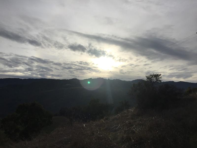 Rays of sunlight break through an sky and shine over a dark expanse