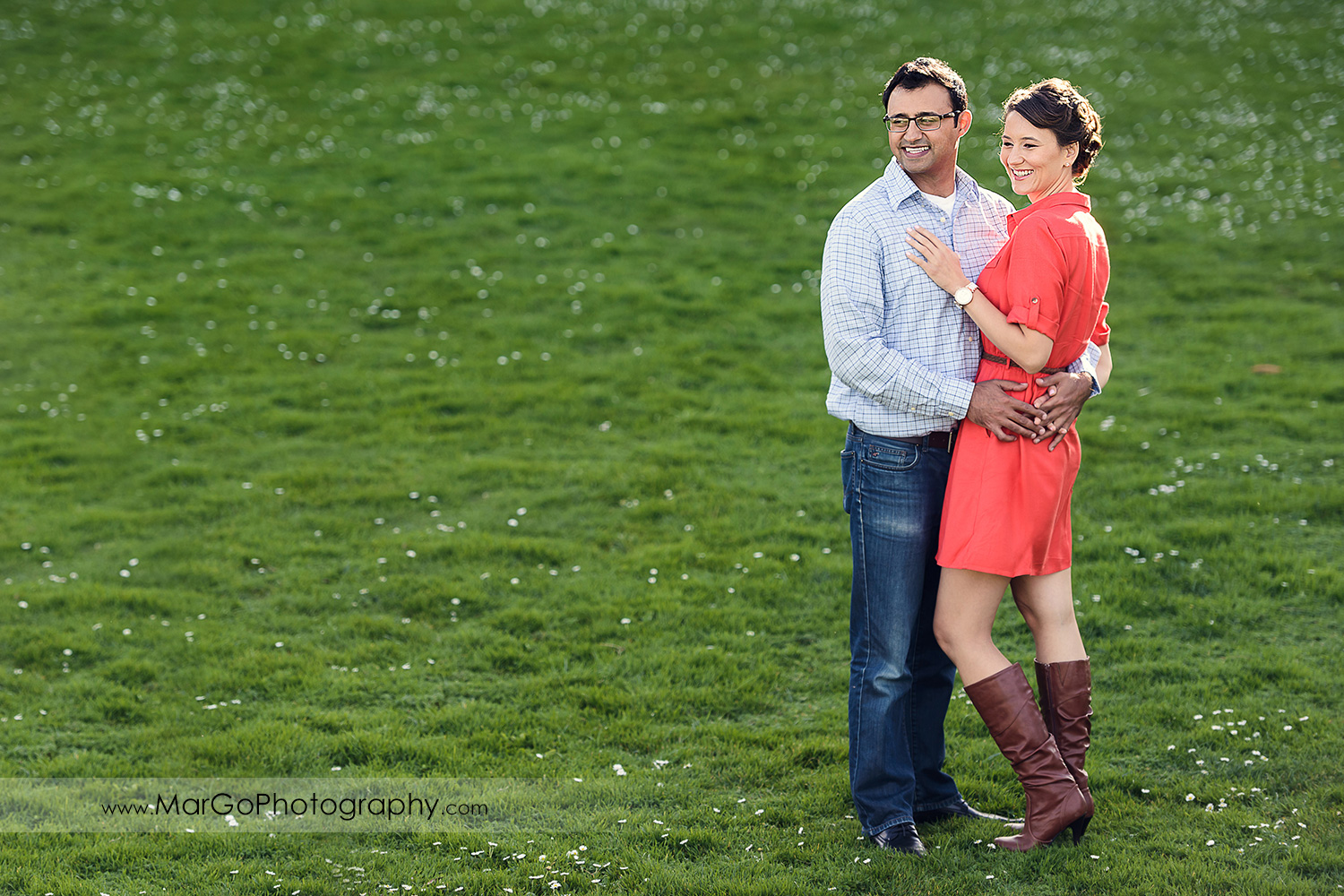 man in blue shirt and woman in red dress standing on the grass during engagement session at San Francisco Legion of Honor