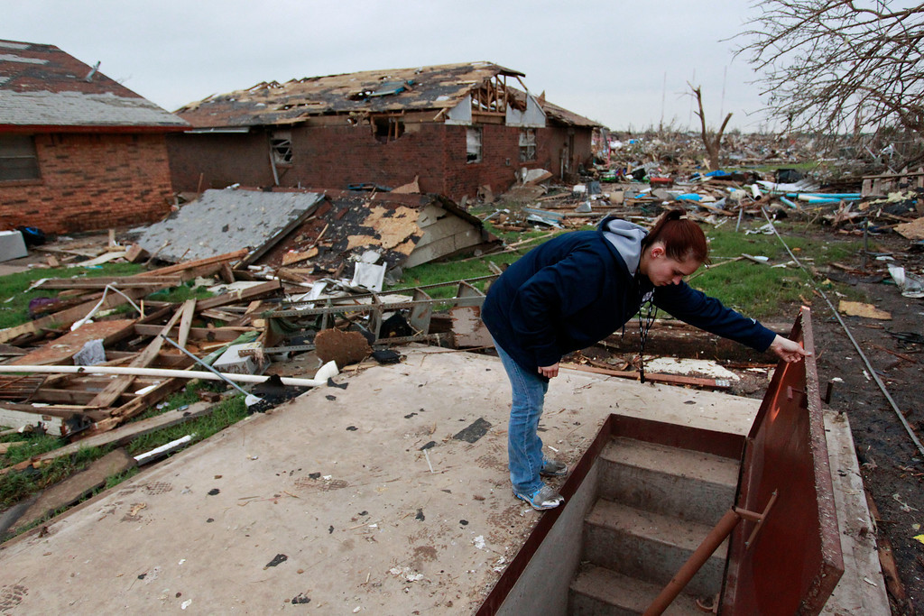 . In this May 24, 2013, file photo, Sabrina Mitchell takes a peek inside a neighbor\'s storm shelter in Moore, Okla.  (AP Photo/Brennan Linsley, File)